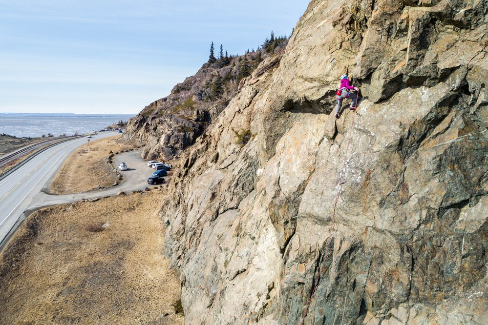 Emily Mahanna leads a route up Sunshine Ridge Saturday, March 31, 2018 along Turnagain Arm. Lead climbing is a rock climbing technique where the climber periodically attaches the rope to anchors as they ascend the route, as opposed to top-roping, where the rope is already secured to the top-most anchor on the route. (Loren Holmes / ADN)