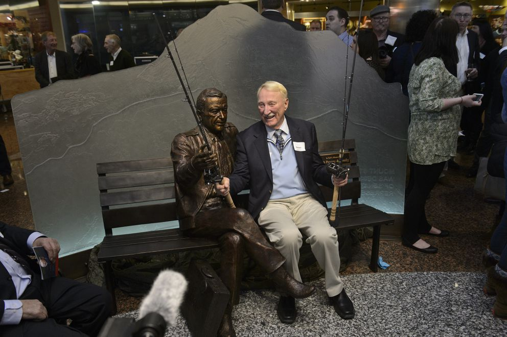 Bob Penney poses with fishing poles at the newly-revealed Ted Stevens statue. (Marc Lester / ADN)