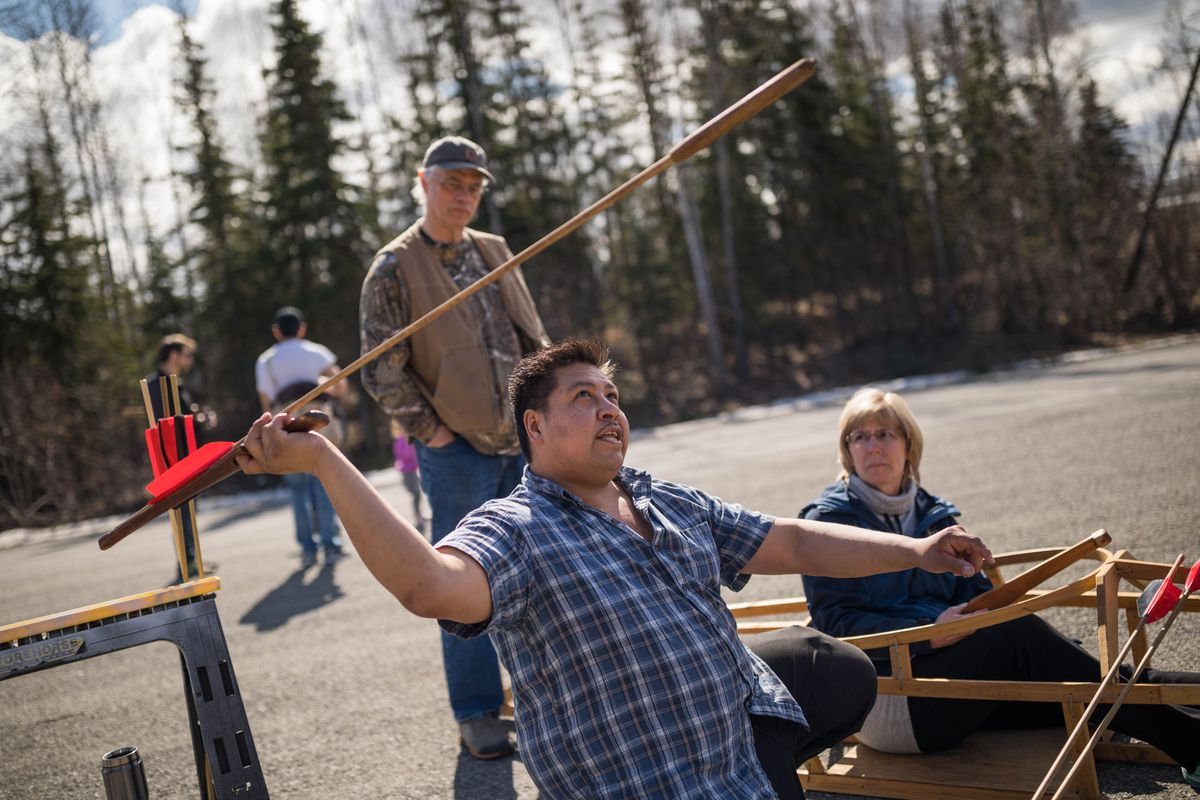 Andrew Abyo demonstrates how to throw a spear-length dart using an atlatl as Cindy and Todd Palmatier watch Saturday at the Alaska Native Heritage Center. (Loren Holmes / Alaska Dispatch News)