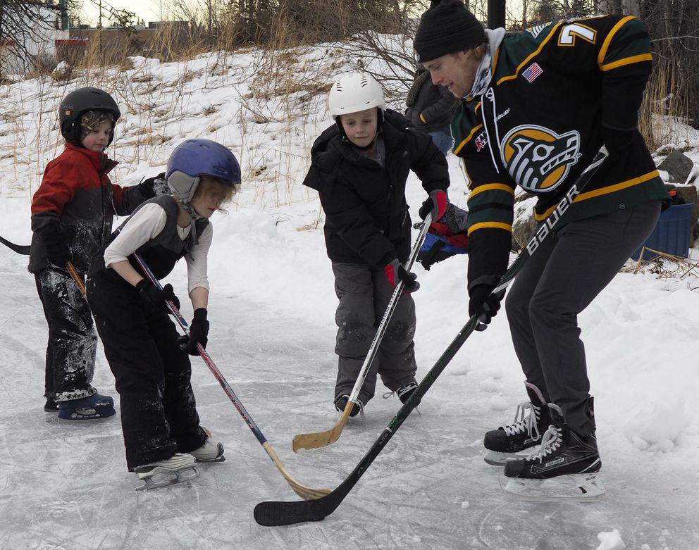 Young skaters pass the puck with UAA hockey player Zac Masson at Chanshtnu Muldoon Park on Monday, January 15, 2018. UAA players joined a celebration of a new skating ribbon there Monday. (Marc Lester / ADN)