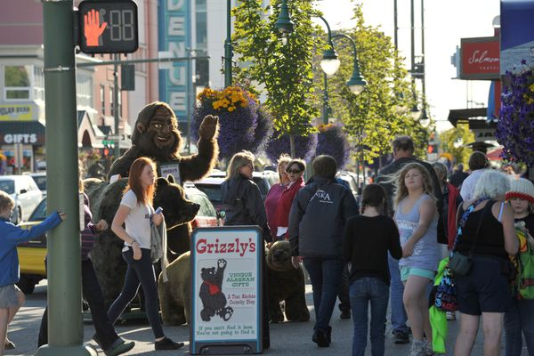 Tourists fill the street in front of Grizzly's Alaskan gift shop, on 4th Avenue, with a Yeti and a life size stuffed bear family on Friday, July 1, 2016. (Bob Hallinen / Alaska Dispatch News)