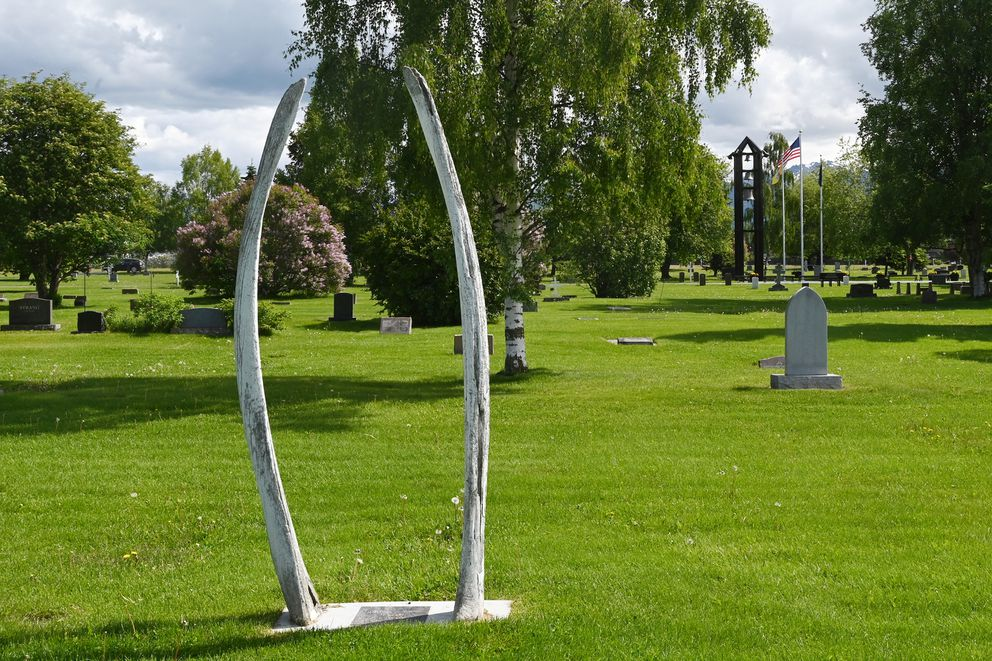 Whale jaw bones mark a grave at Anchorage Memorial Park Cemetery on Sunday, June 21, 2020, with the new bell tower visible in the distance. (Bill Roth / ADN)