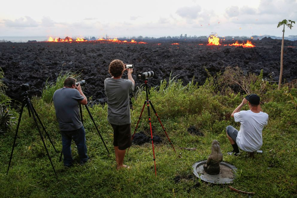 People take photos of a fissure on the outskirts of Pahoa, Hawaii, on Monday. REUTERS/Terray Sylvester