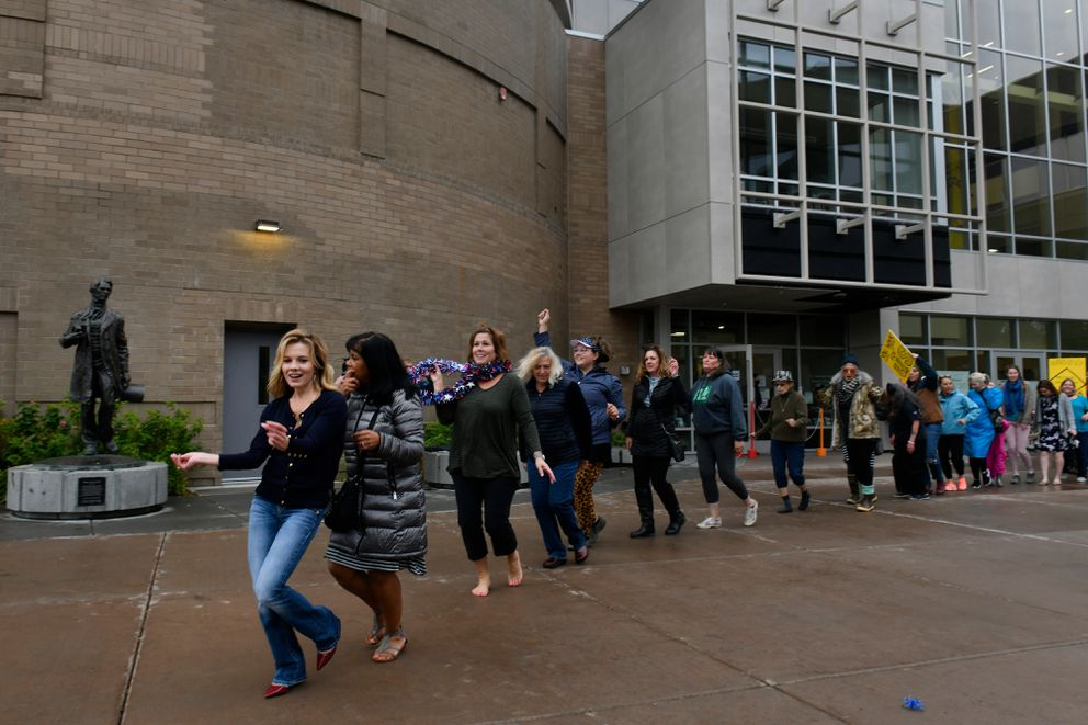 Bernadette Wilson leads a conga line. About 50 people gathered outside the Anchorage Assembly Chambers at the Loussac Library in Anchorage to dance as a form of protest to COVID-19 related business restrictions on September 15, 2020. (Marc Lester / ADN)