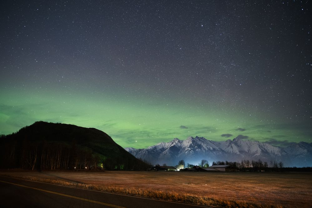A pale band of northern lights is visible over Butte and Matanuska Peak near Palmer on October 20, 2020. (Marc Lester / ADN)