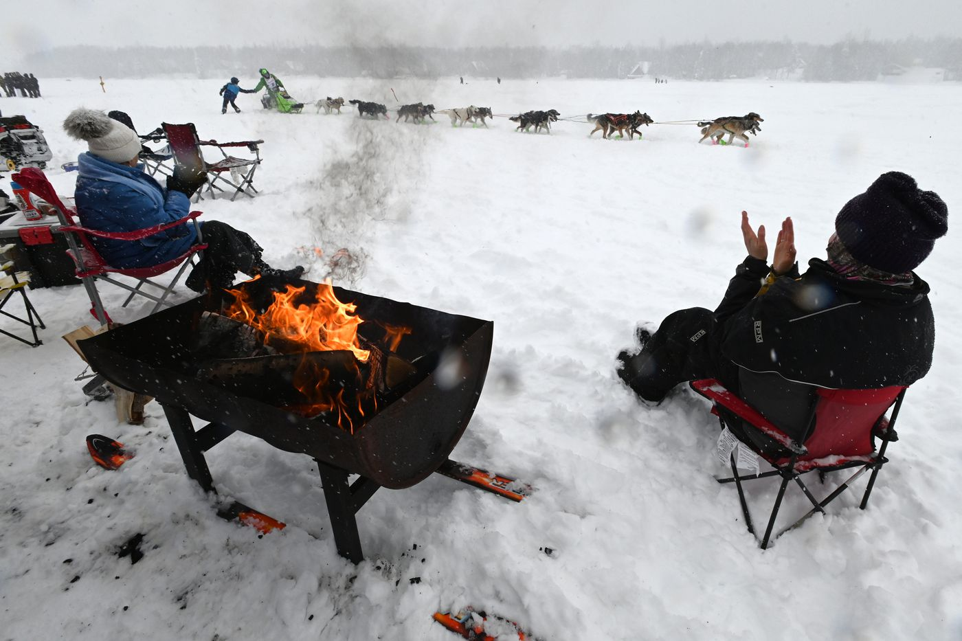Iditarod veteran Ryan Redington connects with a fan while driving his dog team across Long Lake on Sunday. (Bill Roth / ADN)