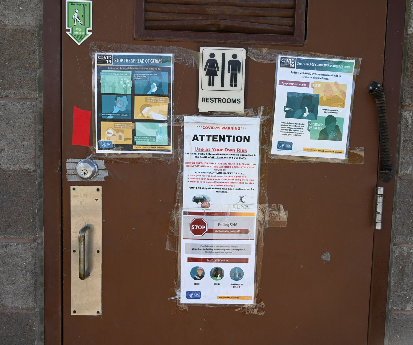 The outhouse doors at the Kenai River are adorned with COVID-19 information. (Anne Raup / ADN)