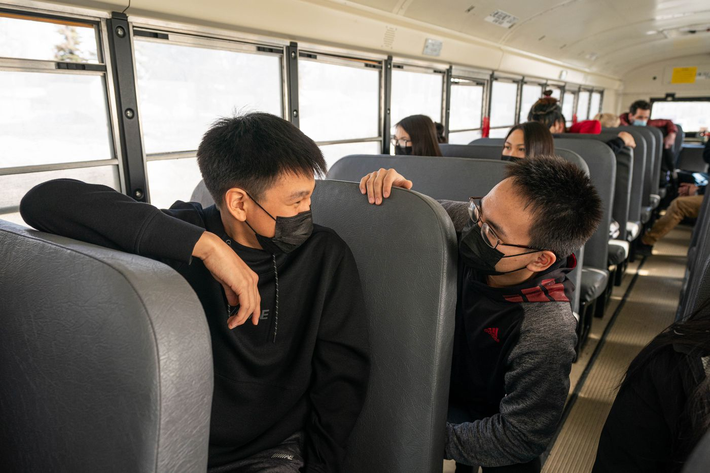 Zachary Isaac, left, and Kyan Paul talk on the school bus after finishing a class at King Tech High School on April 2, 2021. Isaac is from Marshall and Paul is from Pilot Station, which are neighboring villages on the lower Yukon River, and both attend Kusilvak Career Academy in Anchorage. (Loren Holmes / ADN)