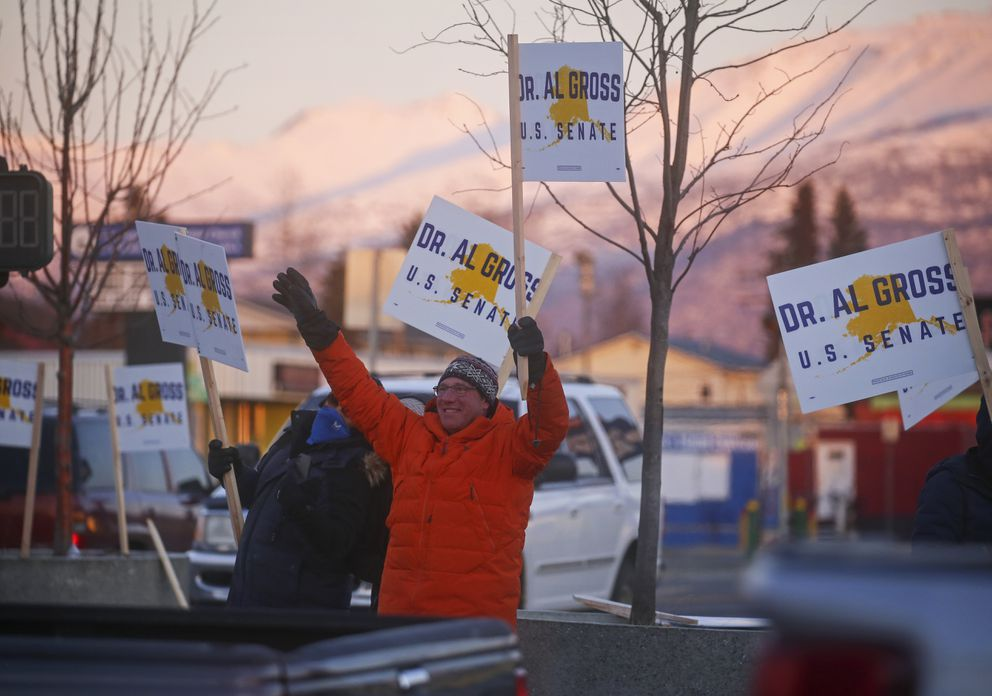 U.S. Senate candidate Al Gross, center, waves to passing cars while waving campaign signs alongside supporters and campaign team members on the corner of North Bragaw Street and Mountain View Drive in Anchorage on Nov. 2, 2020. (Emily Mesner / ADN)
