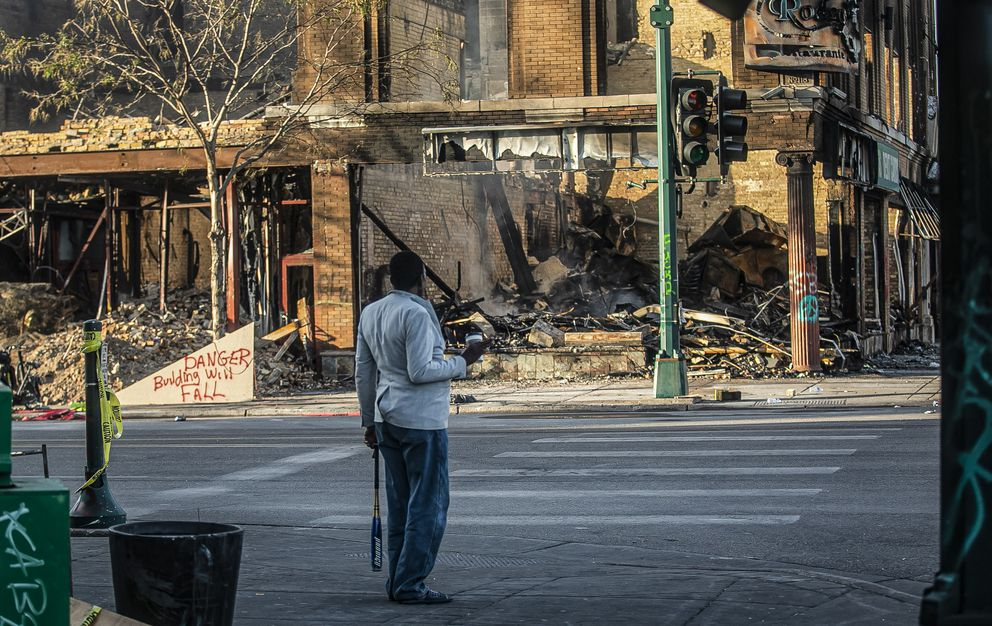 A man looks at the destruction aftermath of businesses along Lake Street, Sunday May 31, 2020, in Minneapolis. Outrage following the death of George Floyd, who died after being restrained by Minneapolis police officers on May 25, has led to the burning of businesses along the the Lake Street corridor where immigrants have found success. (AP Photo/Bebeto Matthews)