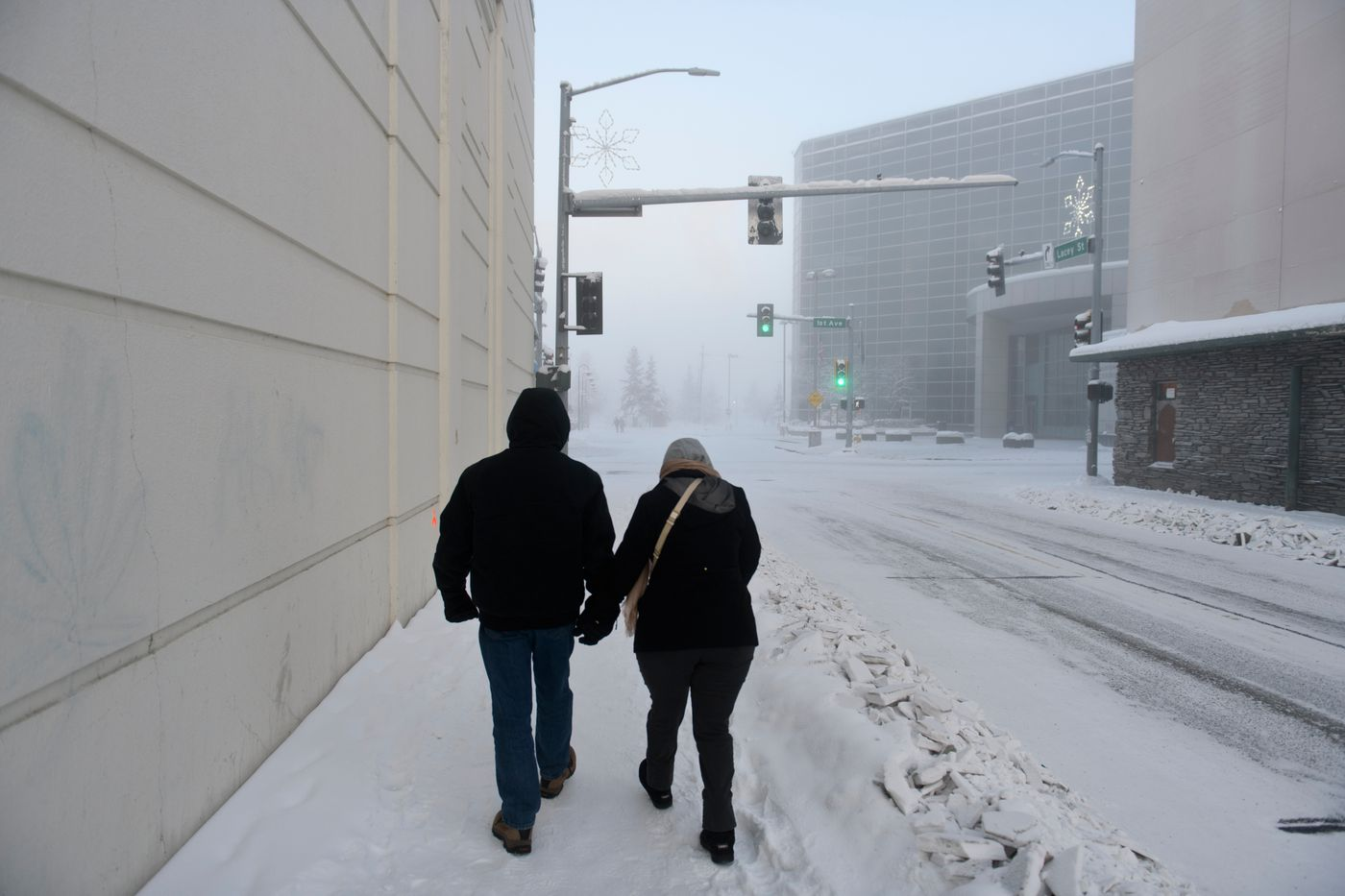 Wayne and Cathy Hofer walk around downtown Fairbanks in temperatures near minus 36 degrees. The Hofers, visiting to see the northern lights, said they probably should've packed more layers of clothing. (Marc Lester / ADN)