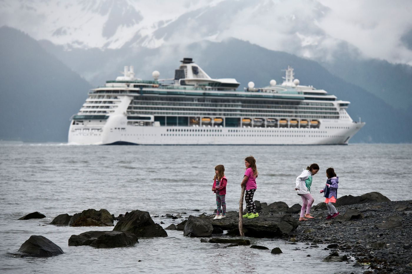 Children play by the Resurrection Bay coastline in Seward asthe Royal Caribbean cruise ship Radiance of the Seas departs on June 22, 2018. The ship traveled Southeast Alaska toward its destination, Vancouver, B.C.(Marc Lester / ADN)