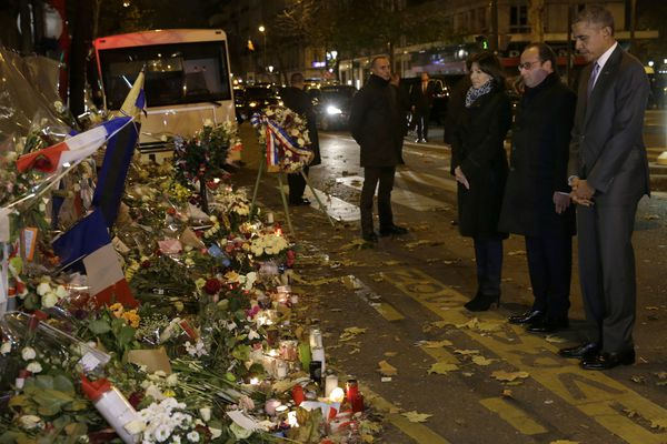 U.S. President Barack Obama, right, French President Francois Hollande and Paris Mayor Anne Hidalgo pay their respect at the Bataclan concert hall, one of the recent deadly Paris attack sites, after Obama arrived in the French capital to attend the World Climate Change Conference 2015.