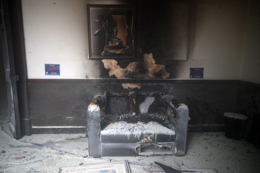 A couch and art work destroyed by fire are seen inside the Congress building after protesters set the building on fire, in Guatemala City, Saturday, Nov. 21, 2020. Hundreds of protesters were protesting in various parts of the country Saturday against Guatemalan President Alejandro Giammattei and members of Congress for the approval of the 2021 budget that reduced funds for education, health and the fight for human rights. (AP Photo/Moises Castillo)