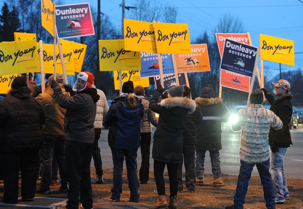 Congressman Don Young supporters and Republican gubernatorial candidate Mike Dunleavy folks wave campaign signs at corner of Northern Lights Boulevard and Seward Highway during the afternoon commute on Election Day, Tuesday, Nov. 6, 2018. (Bill Roth / ADN)
