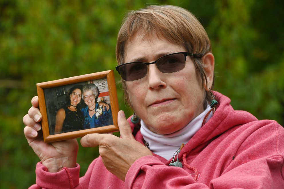 Jeanne Grasser holds a photograph of herself with her mother, Marilyn Grasser, who is a resident at the Alaska Veterans and Pioneers Home in Palmer, in her garden in Sutton on Sept. 8, 2020. 'I would love to have her home for Christmas, ' said Grasser. 'That would be the best gift of all. ' (Bill Roth / ADN)