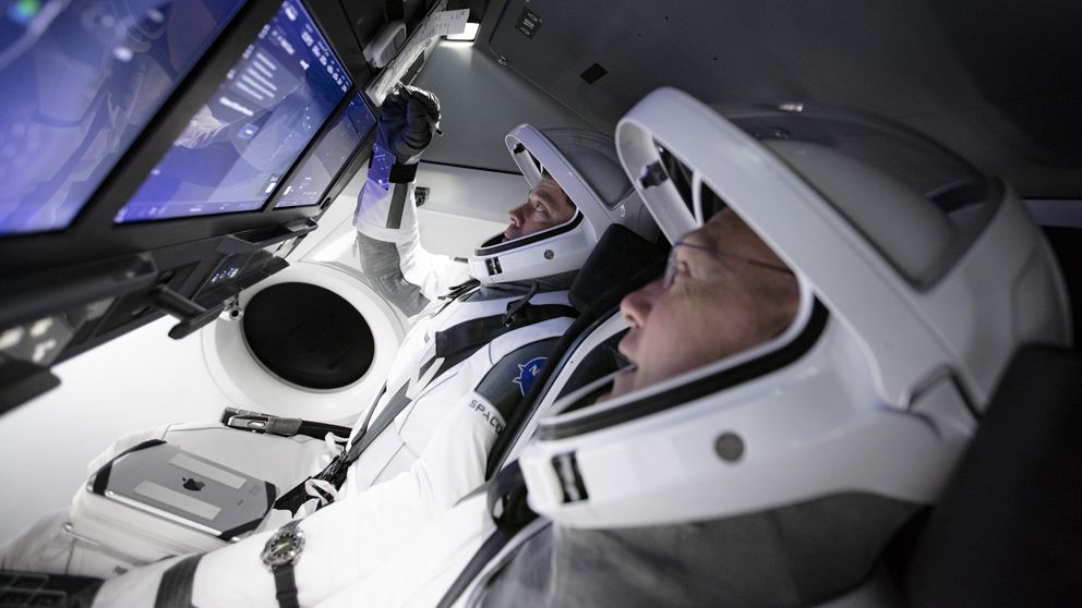 In this Thursday, March 19, 2020 photo made available by SpaceX, astronauts Doug Hurley, foreground, and Bob Behnken work in SpaceX's flight simulator at the Kennedy Space Center in Cape Canaveral, Fla., as SpaceX teams in Firing Room 4 at Kennedy Space Center and the company's Mission Control in Hawthorne, Calif., along with NASA flight controllers in Mission Control Houston, run a full simulation of launch and docking of the Crew Dragon spacecraft. (SpaceX via AP)