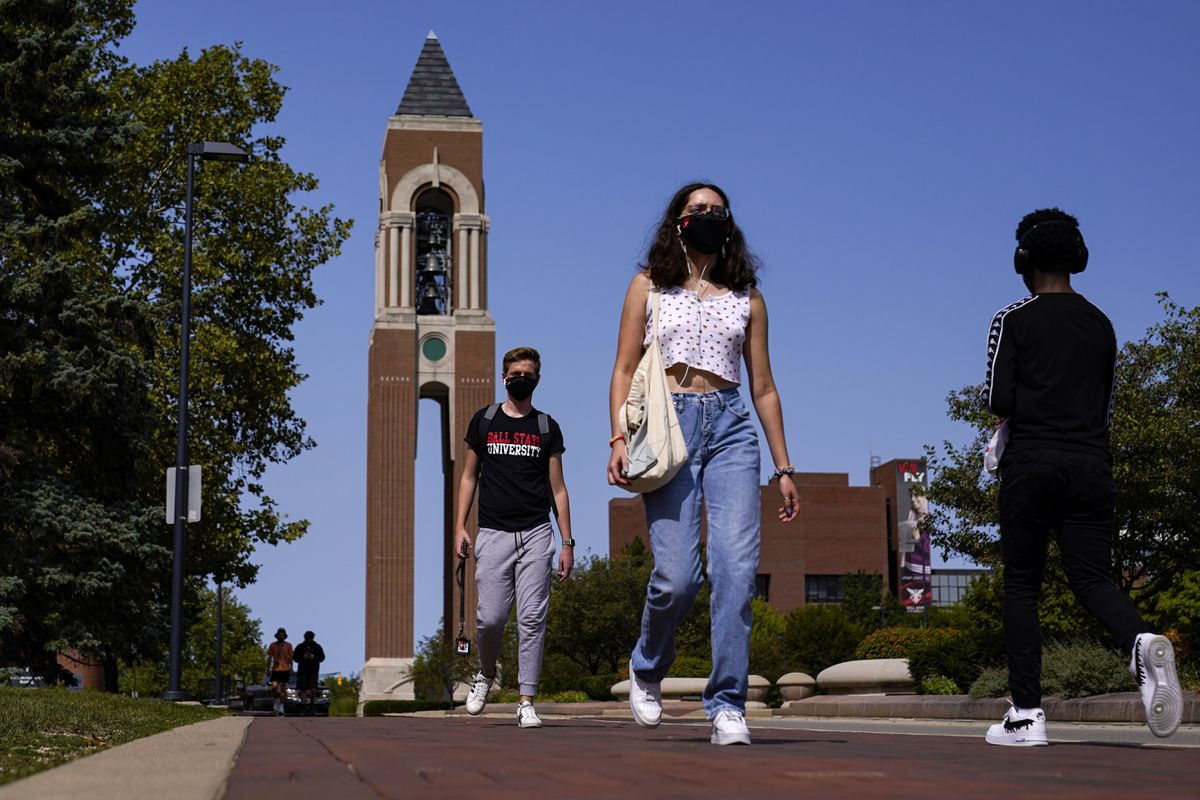 Masked students walk through the campus of Ball State University in Muncie, Ind., Thursday, Sept. 10, 2020. College towns across the U.S. have emerged as coronavirus hot spots in recent weeks as schools struggle to contain the virus. Out of nearly 600 students tested for the virus at Ball State, more than half have returned been found positive, according to data reported by the school. Dozens of infections have been blamed on off-campus parties, prompting university officials to admonish students. (AP Photo/Michael Conroy)