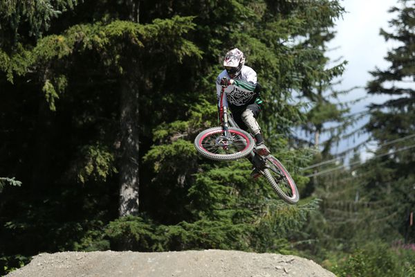 Brandon Rotkis launches off a jump while mountain biking at the Alyeska Bike Park on Sunday July 19, 2015. Lift tickets are available for riders during the summer where they can set their bike on the lift and then ride the chair behind it before they bike down the mountain.