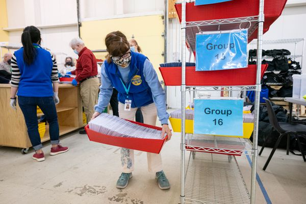 Election worker Bonnie Jack places a tub of ballots on a cart before they are placed in a mail sorting machine on Wednesday, April 7, 2021 at the Municipality of Anchorage election center. The municipality is continuing to count ballots a day after election day. (Loren Holmes / ADN)