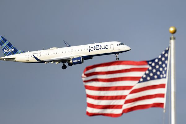 FILE - In this Sept. 21, 2018, file photo, a plane flies past the American flag in Washington. JetBlue plans to join bigger rivals in offering flights between the US and Europe, starting with London in 2021. The move has been rumored for a long time, but the CEO says JetBlue has had to wait for a new Airbus plane that he says will make the flights economical. (AP Photo/Susan Walsh, File)