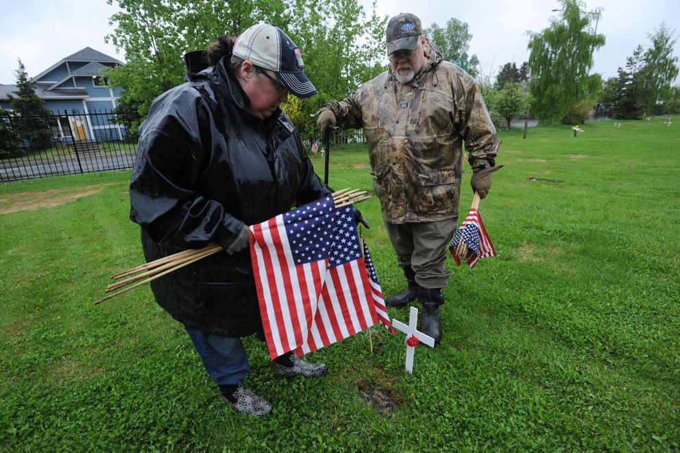 Stacey and Steve Szymanski helped place American flags at the graves of veterans buried at the Anchorage Memorial Park Cemetery on Sunday, May 26, 2019. American Legion Jack Herny Post 1 placed white crosses with a poppies and the Veterans of Foreign Wars Captain James G. Lee Memorial Post 1685 placed American flags. (Bill Roth / ADN)