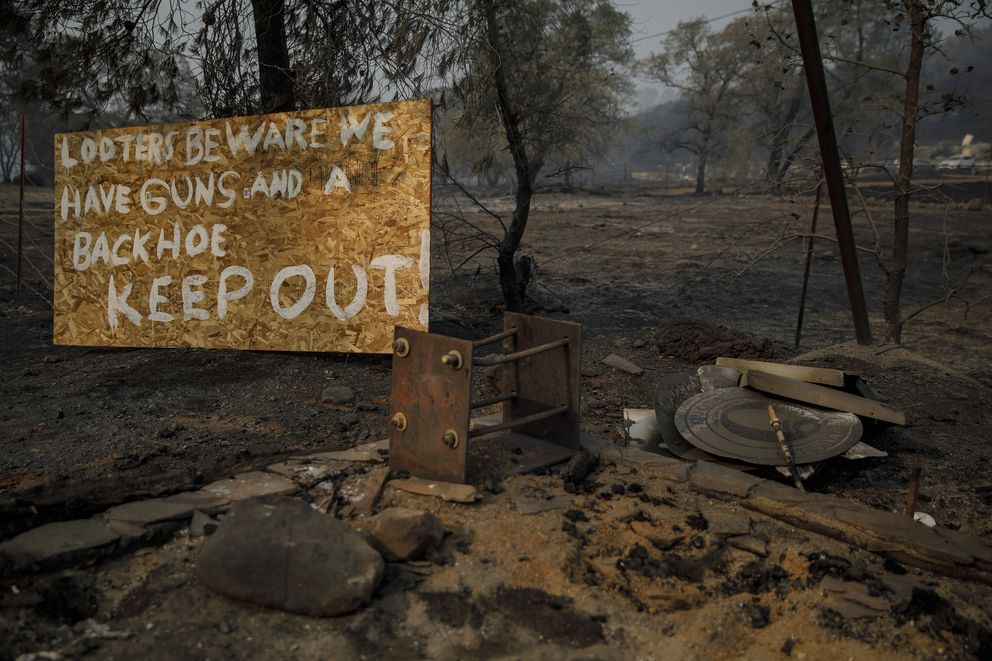 A sign warning to looters sits in the foreground of burned properties in the aftermath of the Camp fire that tore through Paradise, Calif., on Friday, Nov. 16, 2018. (Marcus Yam/Los Angeles Times/TNS)