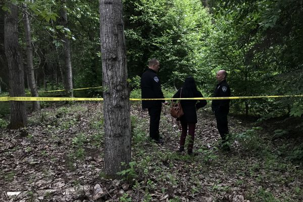 Anchorage Police officers and Assistant District Attorney Saritha Anjilvel near the scene of a shooting that occurred in the woods off the Chester Creek Trail near Sullivan Arena, which left one male dead and another severely injured Sunday evening, June 2, 2019.