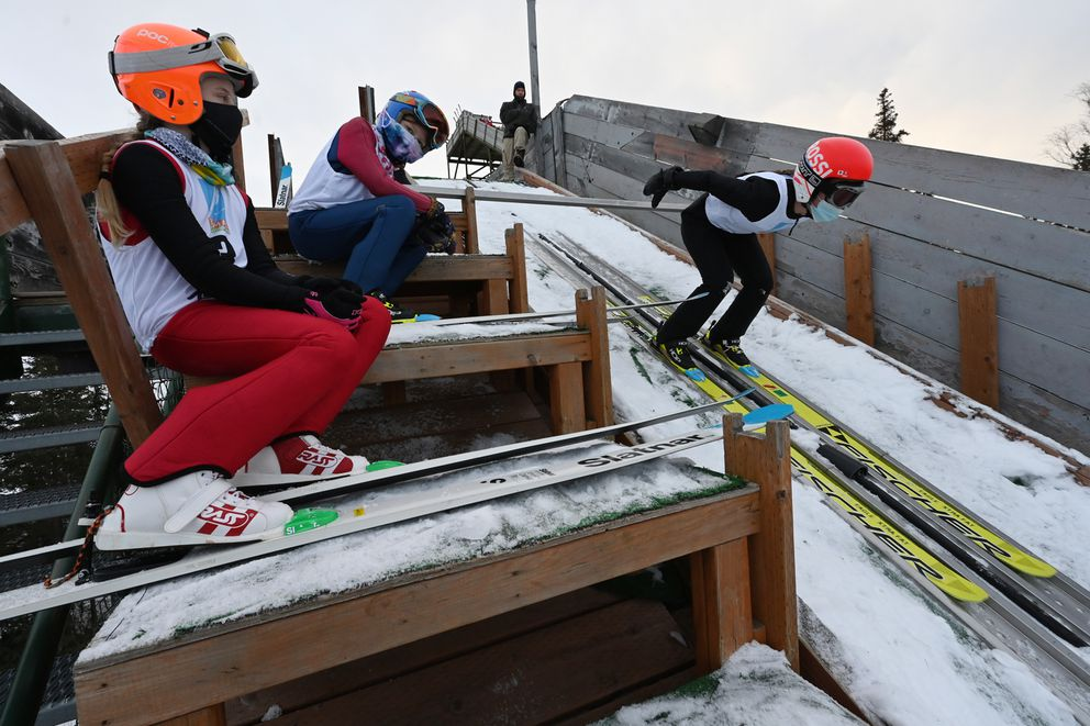 Jane Malouf skis down the in-run on the 40-meter jump while Julia Oswald, left, and Jamay Wingard, center, wait to jump. (Bill Roth / ADN)