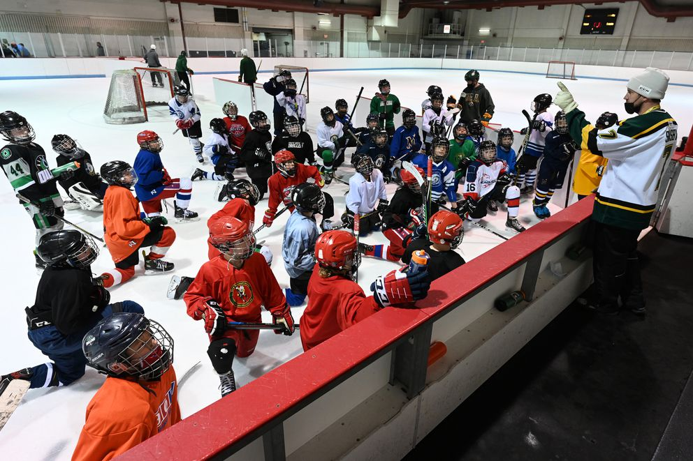 Former UAA defenseman Matt Shasby, right, talks to players Sunday at the Dempsey Anderson Ice Arena. (Bill Roth / ADN)