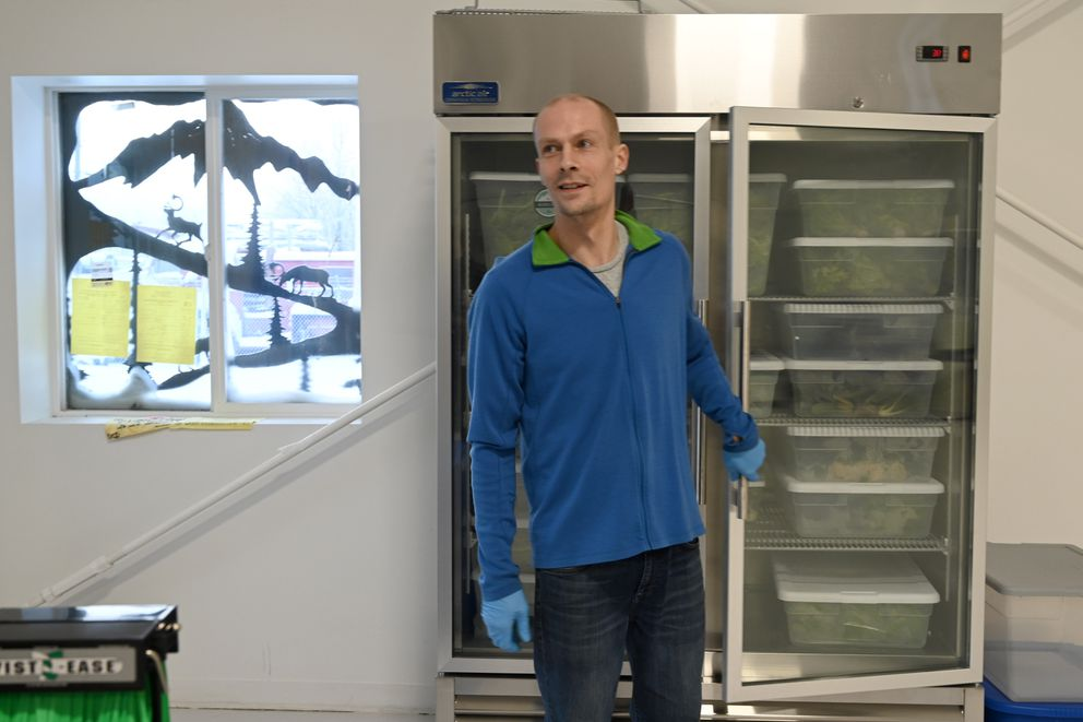 Business owner Trevor Kirchhoff closes the cooler door at Anchorage Greens, Jan. 3, 2020. (Anne Raup / ADN)