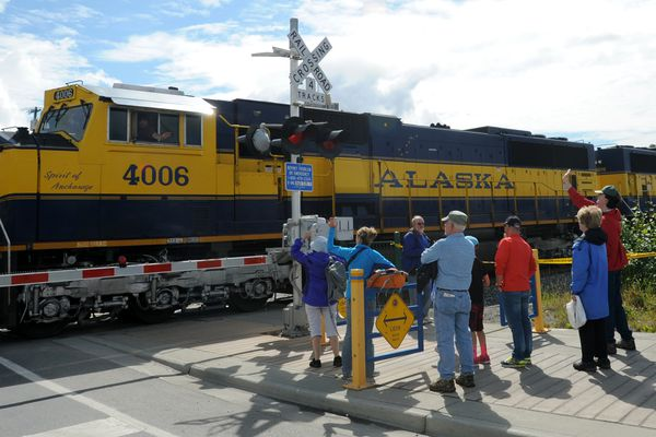 Tourists wave as an empty Alaska Railroad gravel train heads back to Mat-Su for more cargo on Monday afternoon, June 20, 2016, at Ship Creek. (Erik Hill / Alaska Dispatch News)