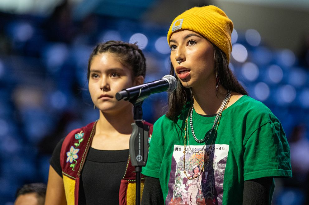 Quannah Chasinghorse, 17, right, and Nanieezh Peter, 15, speak in support of a resolution reinstating a climate action leadership task force and declaring a state of emergency on climate change, on Oct. 19, 2019 during the Alaska Federation of Natives convention at the Carlson Center in Fairbanks. (Loren Holmes / ADN archive)