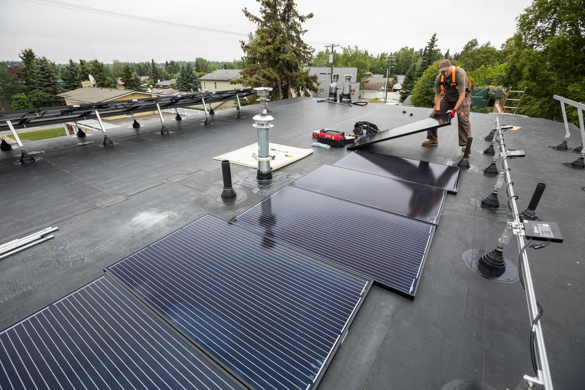 Ben May arranges solar panels atop a home in Anchorage's south addition neighborhood Friday, July 20, 2018. May owns Anchorage Solar, and says the 20-panel array should offset 60-90 percent of the homeowner's electrical use. (Loren Holmes / ADN)