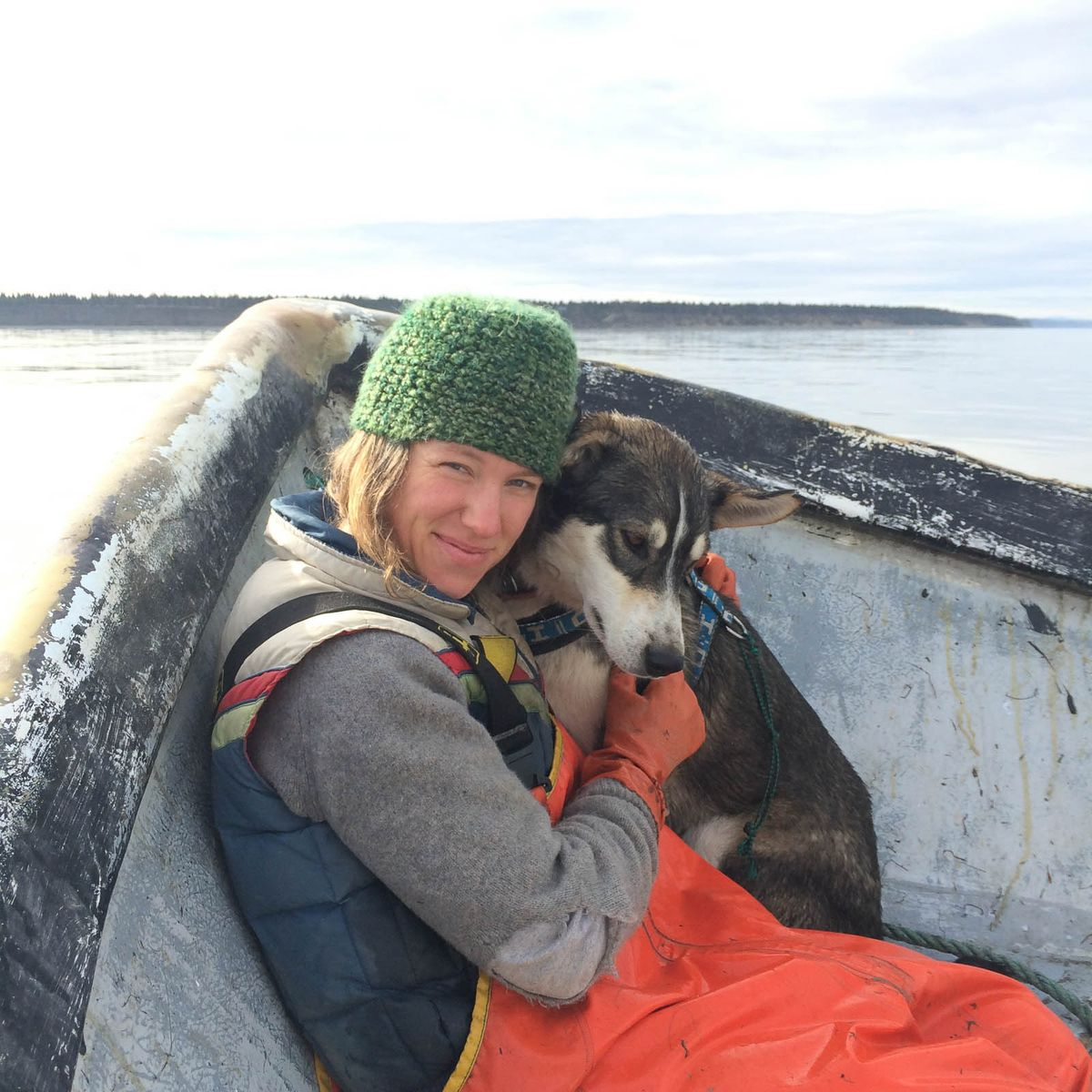 Kasilof-based Iditarod musher Monica Zappa cuddles with one of her lead sled dogs, Dweezil, during fishing season. She and longtime musher Tim Osmar fish a setnet site in Cook Inlet. (Monica Zappa photo)