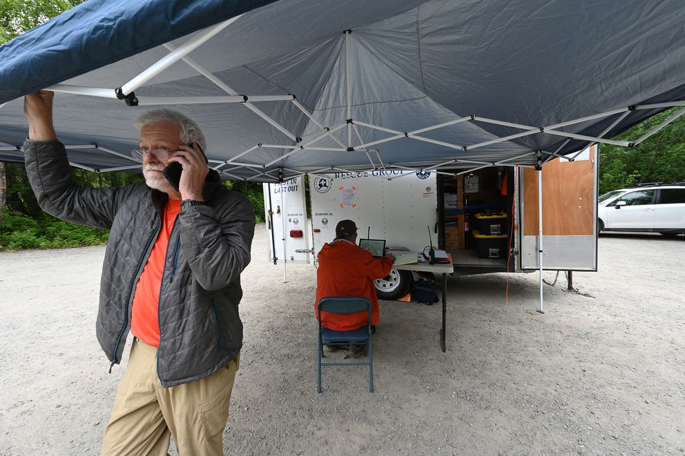 Bill Laxson with the Alaska Mountain Rescue Group and Tom Plawman of the Alaska Incident Management Team work from the parking lot of Pioneer Ridge Trail trailhead on Wednesday, June 16, 2021, as the search continued for a missing woman who encounter bears early Tuesday. (Bill Roth / ADN)