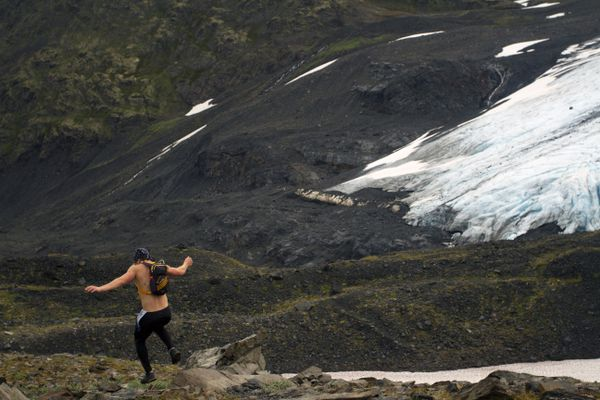 A runner jumps off a rock as he descends Crow Pass during the 33rd annual Crow Pass Crossing from Girdwood to Eagle River on Saturday, July 23, 2016. Racers ran 22.5-miles through the wilderness, which included crossing a river. (Sarah Bell / Alaska Dispatch News)