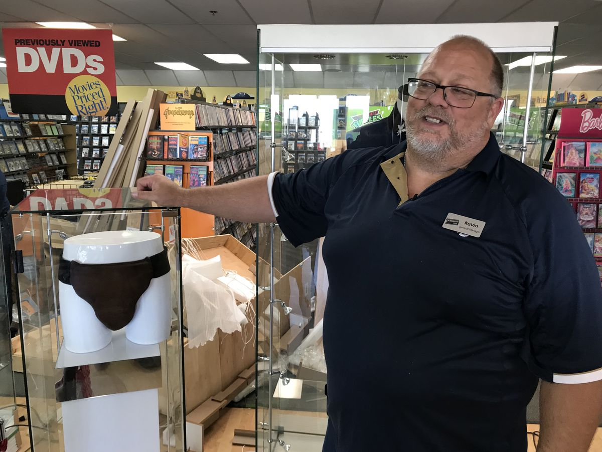 "General manager Kevin Daymude poses with Russell Crowe movie memorabilia at the Blockbuster store on DeBarr Road in Anchorage on Wednesday, May 2, 2018. Pictured at left is the leather jockstrap Crowe wore in the movie ""Cinderella Man."" (Bill Roth / ADN)"