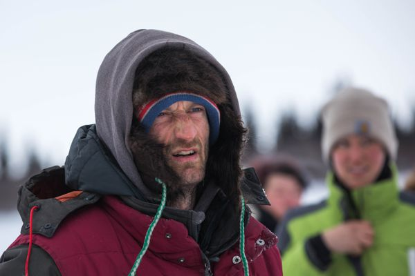 Nicolas Petit looks at his dog team after arriving in White Mountain on Tuesday, March 13, 2018. (Loren Holmes / ADN)