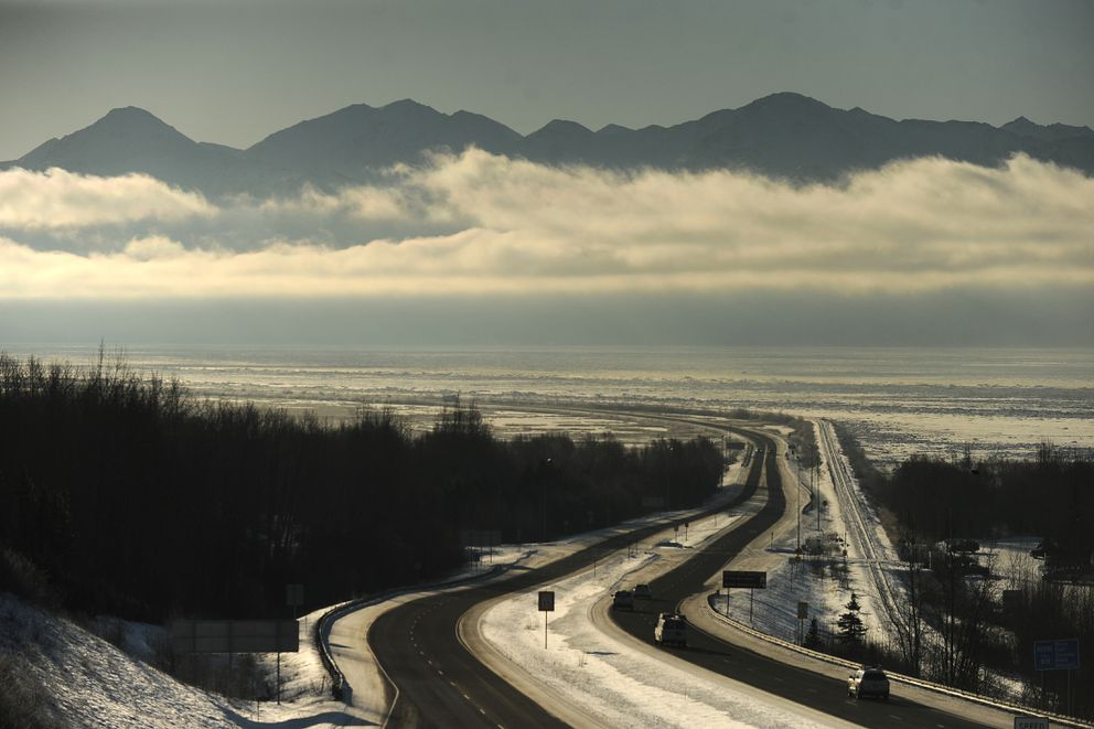 A low band of clouds hangs over Turnagain Arm in front of the Kenai Mountains as the Seward Highway heads out of Anchorage, AK on Thursday, Feb. 8, 2018. (Bob Hallinen / ADN)