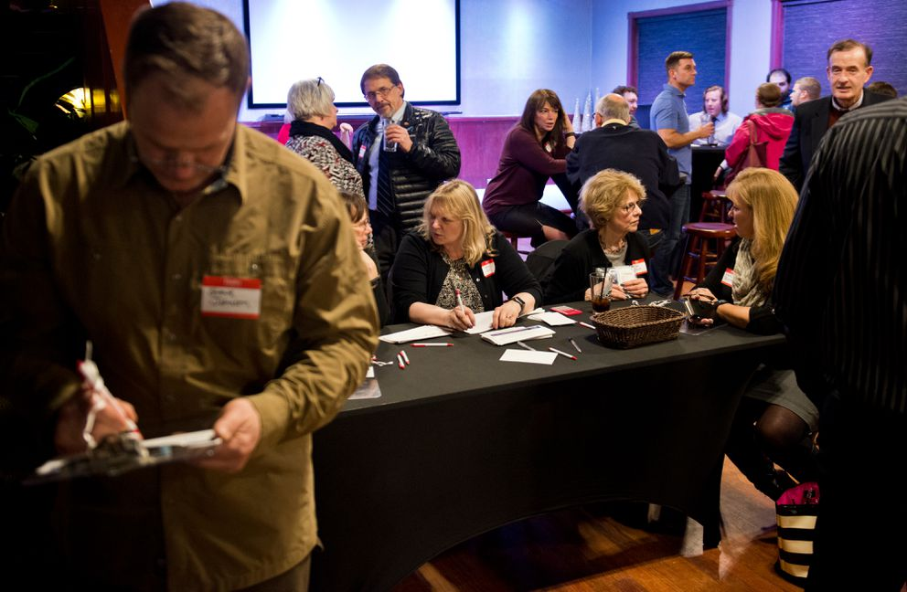 Guests sign in and make donations at a front table at a fundraising event for Republicans at the Hangar on the Wharf event hall.  (Marc Lester / Alaska Dispatch News)