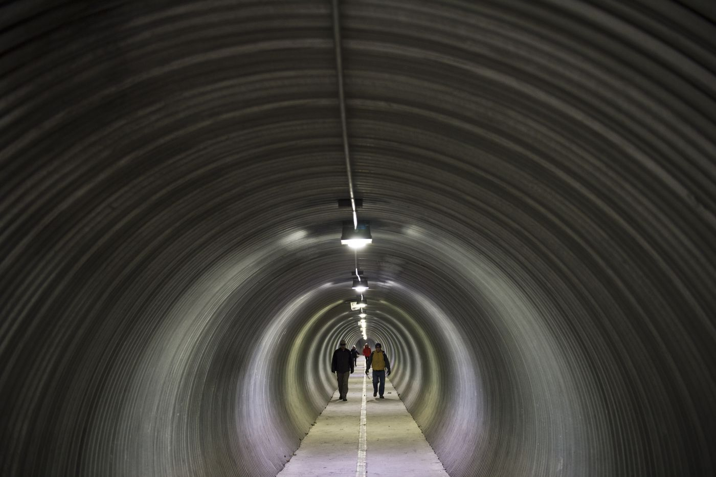 Whittier residents walk through a pedestrian tunnel under the rail yard on Oct. 10. The tunnel connects the harbor to the city center. (Marc Lester / Alaska Dispatch News)