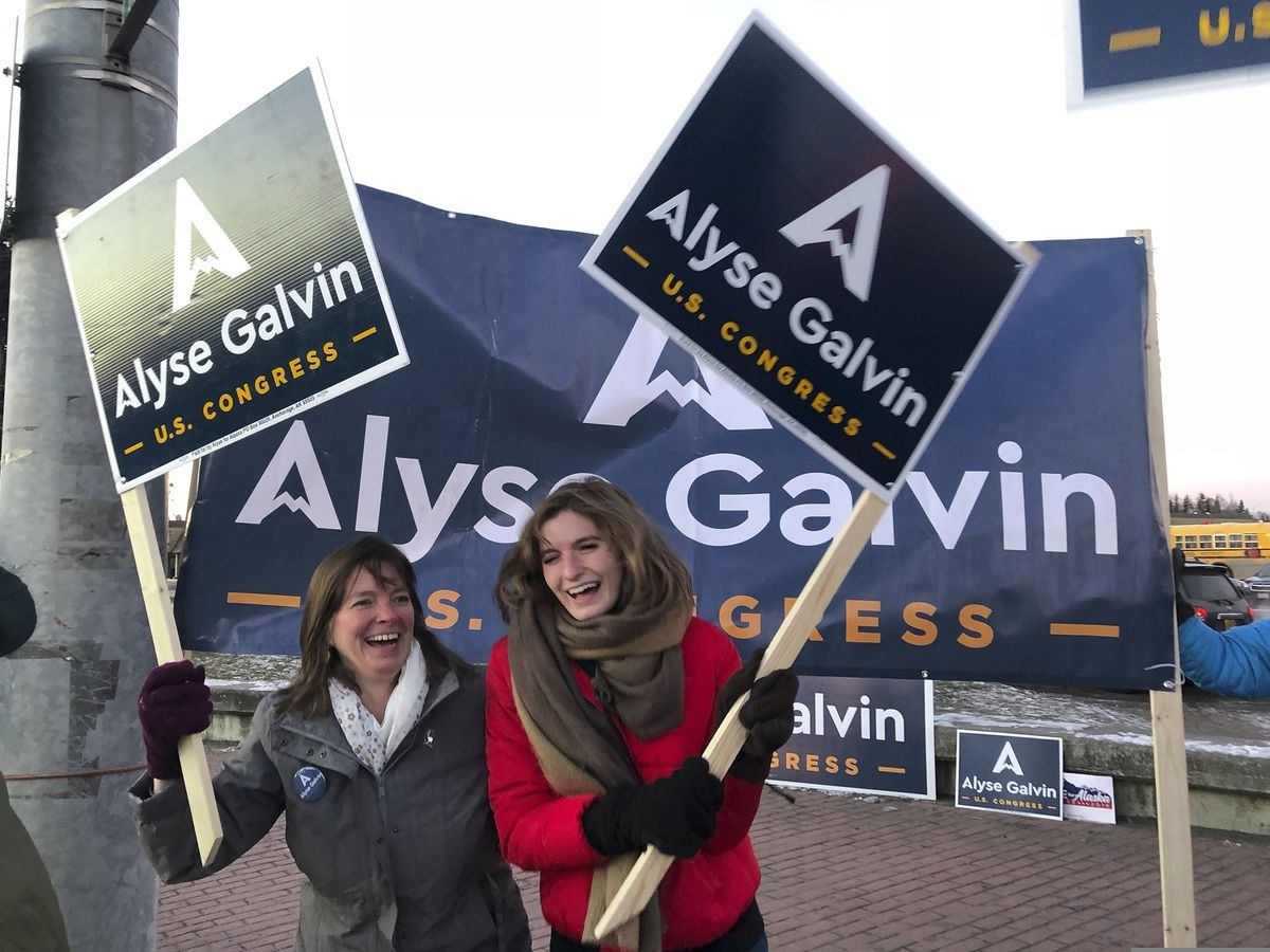 In this Nov. 5, 2018, file photo, Alaska U.S. House candidate Alyse Galvin, left, and her daughter Bridget wave signs on the corner of a busy street in Anchorage. (AP Photo/Becky Bohrer, File)