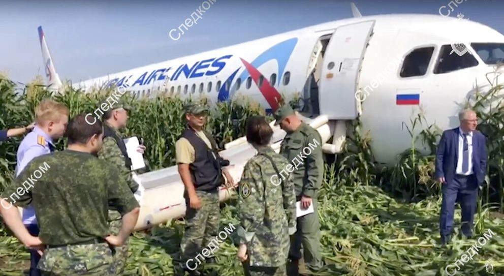 In this file image taken from a video distributed by Russian Investigative Committee, employees work at the crash site of a Russian Ural Airlines' A321 plane after an emergency landing in a cornfield near Ramenskoye, outside Moscow. (Via AP)