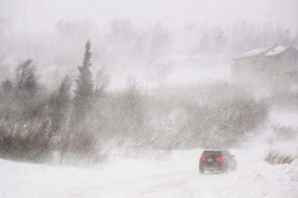 A vehicle drives along Kings Way Drive as strong winds tear through Bear Valley in Anchorage on Tuesday, Dec. 22, 2020. (Emily Mesner / ADN)