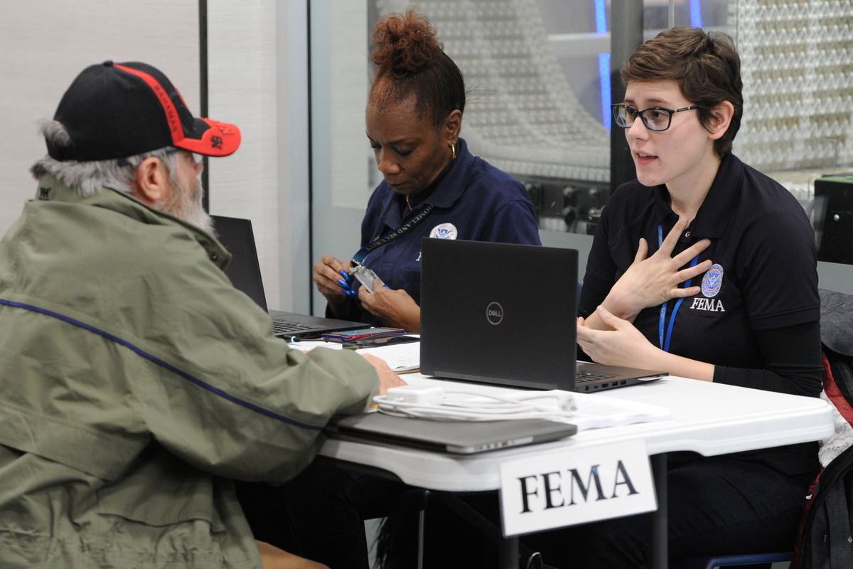 Steve Bye, left, inquires about disaster assistance through FEMA for his earthquake damaged home on Sunday, Feb. 10, 2019, at the Loussac Library. (Bill Roth / ADN)