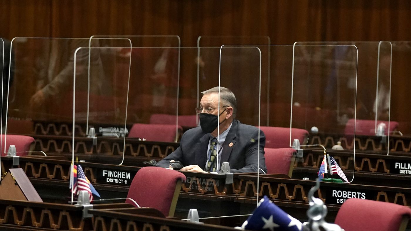 Wearing a face covering and sitting among socially-distanced plexiglass, Rep. Mark Finchemsits at his desk during the opening of the Arizona Legislature at the state Capitol, Monday, Jan. 11, 2021, in Phoenix. (AP Photo/Ross D. Franklin, Pool)