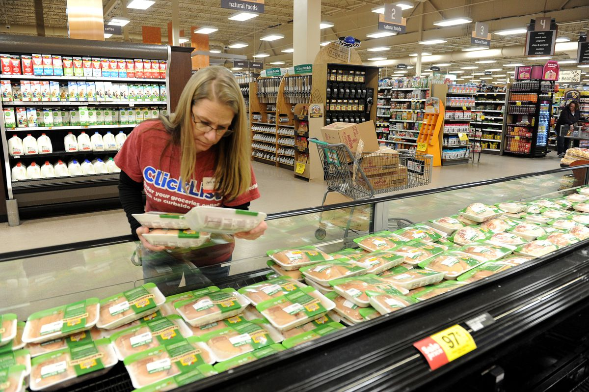Jen Kelsey inspects chicken as she shops for a customer at the Northern Lights Fred Meyer in Anchorage in 2017. (Bob Hallinen / ADN)
