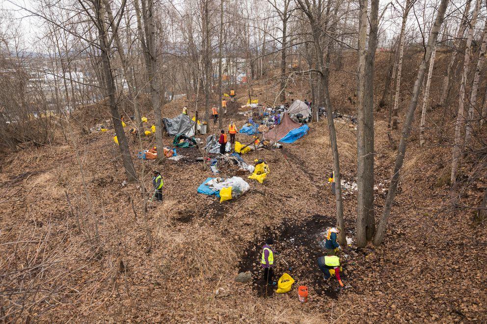 Volunteers pick up trash at the homeless camp. (Loren Holmes / ADN)