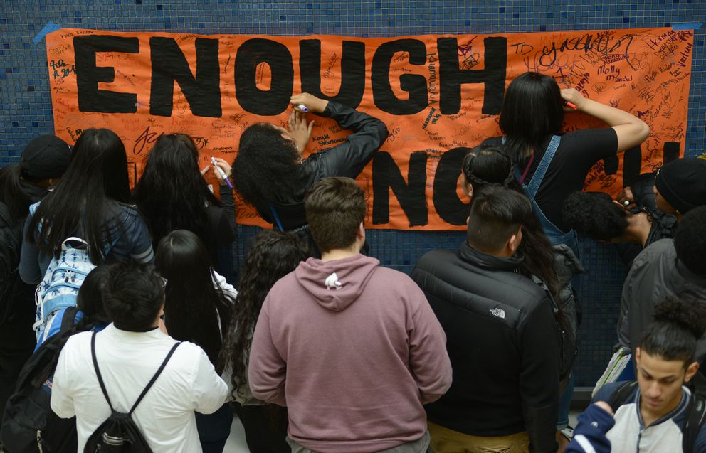 Students sign the Enough is Enough poster after the speaker portion of the sit-in program. Around 400 students participated at Bartlett High School Friday morning, April 20, 2018 as part of the National School Walkout. (Anne Raup / ADN)